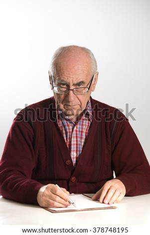 old seniour man wearing eyeglasses, working with documents, using pen looking serious wearing red sweater - stock photo