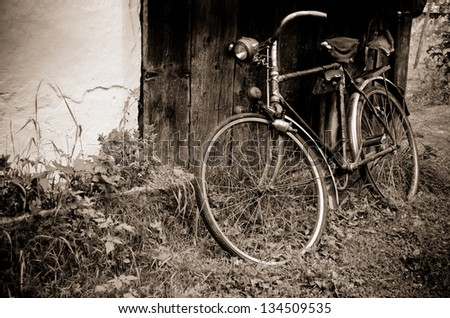 Old sepia vintage bicycle near the house in the village - stock photo