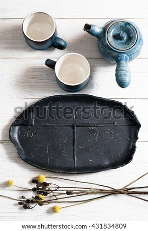 old set of dishes and accessories for the tea ceremony . Top view on two clay tea mugs, old clay teapot and black plate. Rustic served tea-party for two - stock photo
