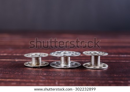 old sewing machine bobbins on wooden background