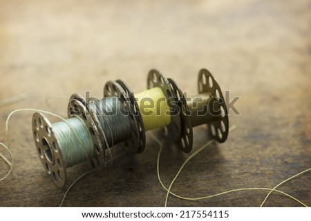 Old sewing machine bobbins with blue and yellow threads, on a old grungy work table. - stock photo