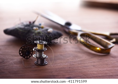 Old sewing machine bobbins,  with gold ( brass ) scissors and pin cushion on a old grungy work table. Tailor's work table. textile or fine cloth making.Shallow depth of field. - stock photo