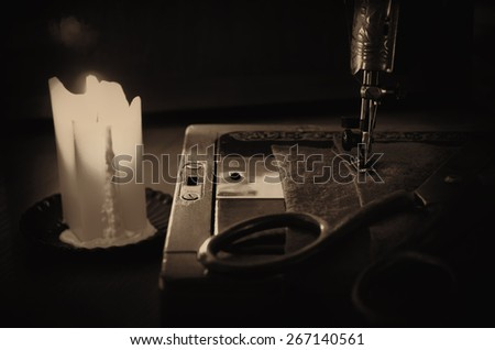 old sewing machine, fabric and rusty scissors at the light candle. close up, horizontal, sepia, low key - stock photo