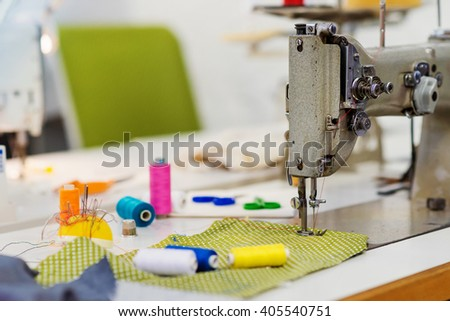 Old sewing machine, threads, pins and piece of fabric - stock photo