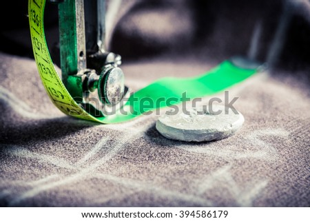Old sewing machine with scissors, cloth and threads - stock photo
