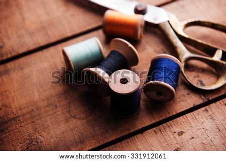 Old sewing thread wooden reels or bobbins and a gold scissors on a old rustic work bench. Intentionally shot in muted retro-vintage tone and shallow depth of field. (soft focus) - stock photo