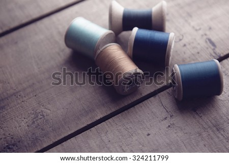 Old sewing thread wooden reels or bobbins on a old rustic work bench. Intentionally shot in muted retro-vintage tone and shallow depth of field. (soft focus) - stock photo