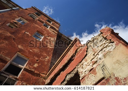 Old shabby abandoned building of red bricks against clear blue sky