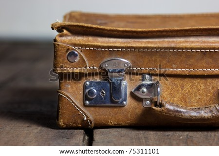 old shabby leather portable suitcase for travel trip on floor - stock photo