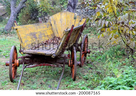 Old shabby wooden yellow cart in the garden - stock photo