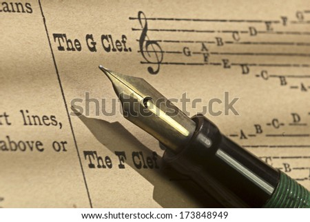 Old sheet music on aged paper, with vintage fountain pen. - stock photo