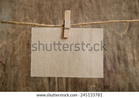 Old sheet of paper hanging on the clothesline on clothespin . On old wood background. - stock photo