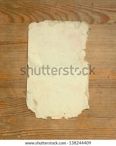 Old sheet of paper on a wooden background.