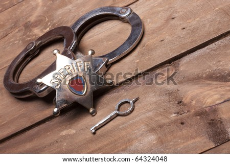 old sheriff badge and handcuffs - stock photo