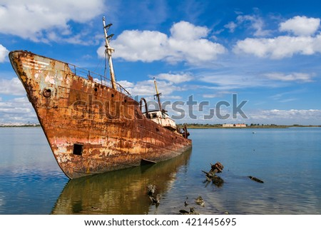 Old ship run aground and rusting in the shore. Seixal, Portugal. - stock photo