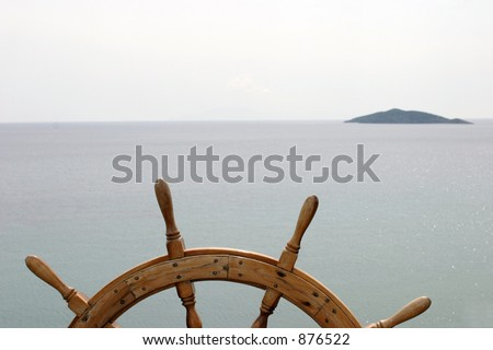 Old ship's steering wheel on great ocean background with a small island ahead. - stock photo