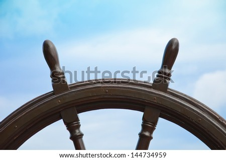 old ship wheel with blue sky background - stock photo