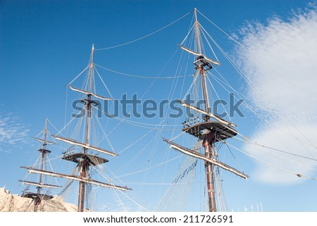 Old ship wooden mast against blue sky - stock photo