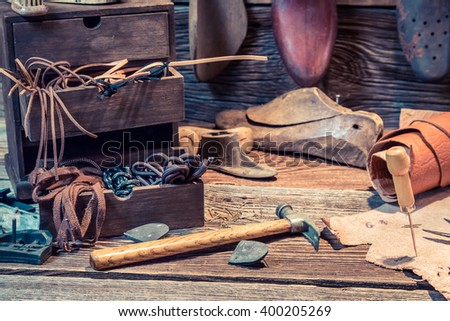 Old shoemaker workshop with brush and shoes - stock photo