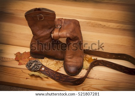 old shoes and leather belt on wooden board