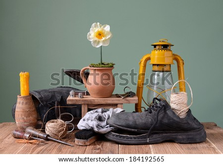 Old shoes and shoemaker tools on the table - stock photo