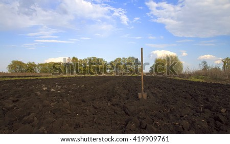old shovel stuck in the box of the dug earth in the garden - stock photo