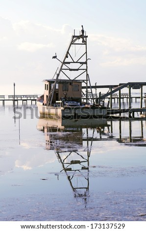 Old shrimp boat sits a dock in the early morning in Corpus Christi Bay, Texas - stock photo
