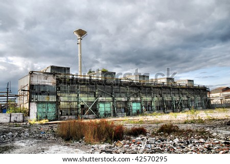 Old shut down factory is overshadowed by dark stormy clouds