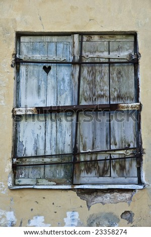 old shutter doors on a window with a small decorative heart - stock photo