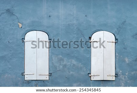 Old Shutters over Windows on a Grunge Wall - stock photo