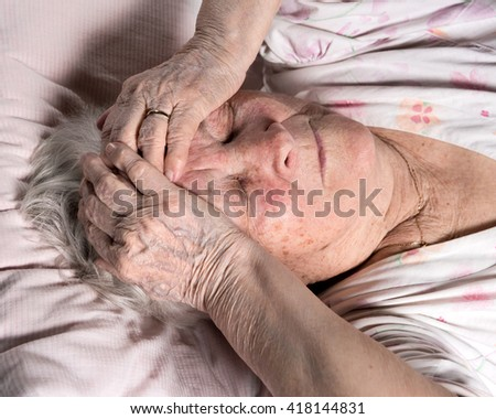 Old sick woman lying in bed at home - stock photo