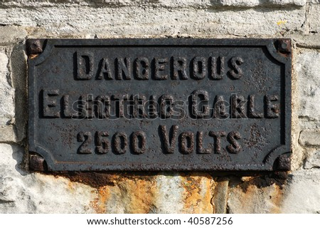 Old sign warning of a high voltage electric cable.