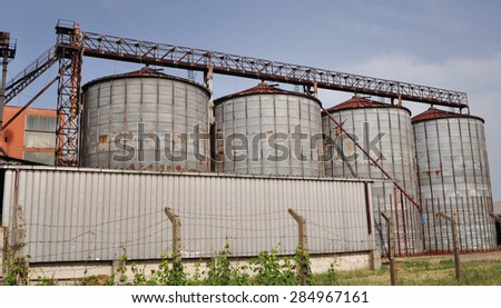 Old silos for storing crop in the collective farm land - stock photo