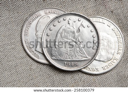Old silver dollar USA coin and German Reich 5 mark coins - stock photo