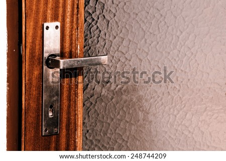 old silver door handle on the doors from wood and glass - stock photo