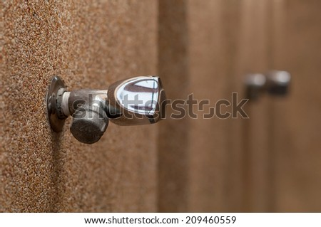 old Silver faucet on brown wall - stock photo