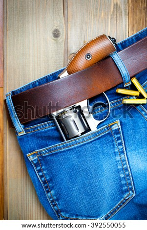 old silver revolver and vintage blue jeans with a leather belt - stock photo