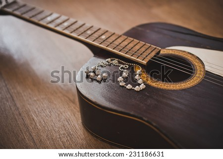 Old six-string guitar and ornaments on it. - stock photo