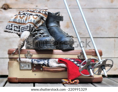 old ski boots on a small  suitcase full of warm clothes - stock photo