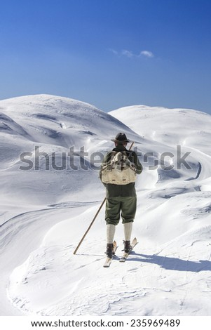Old skier with traditional old wooden skis and backpack - stock photo