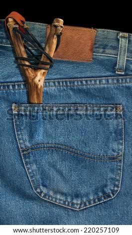 Old Slingshot in Denim Pocket / Old handmade slingshot in the back pocket of blue jeans - stock photo