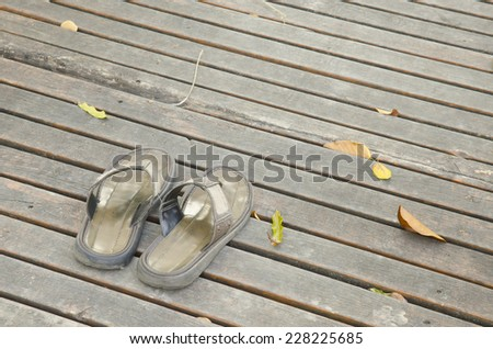 Old Slippers shoes on wooden floor - stock photo