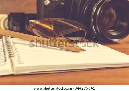 Old SLR camera on the table next to negative film strip, and in the foreground a notebook and pencil. Selective focus on pencil. - stock photo