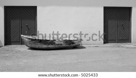 Old small boat next to the door in the street - Comillas, Spain.