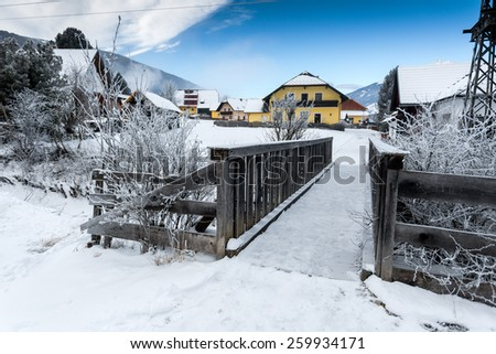 Old small wooden bridge over mountain river in Alps at snowy day - stock photo