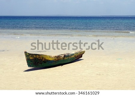 Old small wooden fishing boat on white beach, Indian  Ocean - stock photo