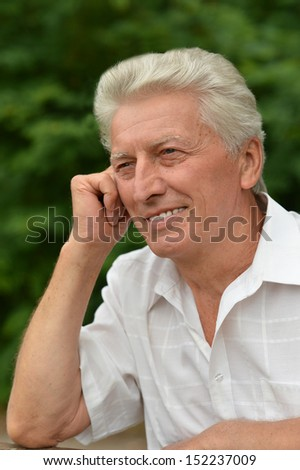 Old smiling man out for a walk in the park in summer - stock photo