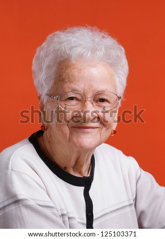 Old smiling woman in glasses on orange background