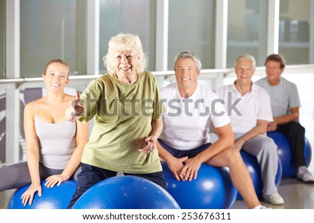 Old smiling woman in gym holding her thumbs up in fitness class - stock photo