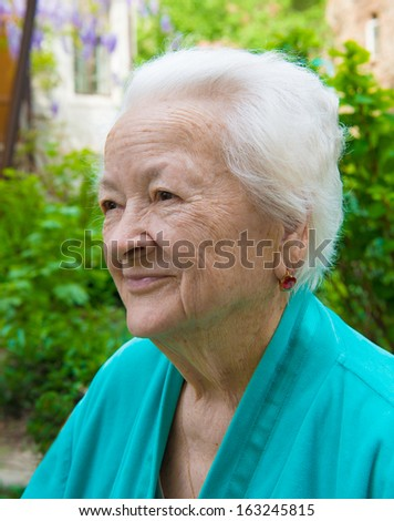 Old smiling woman on nature background